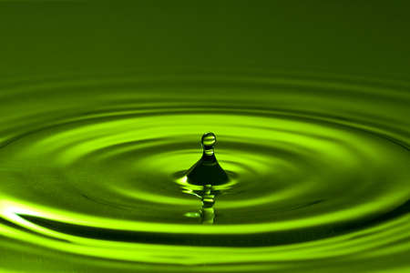 droplet splash in a green clean water  Stock Photo