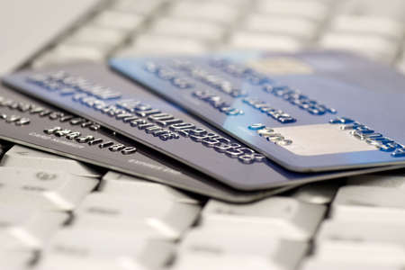 credit card debt: e-commerce concept. group of credit cards and laptop with shallow DOF