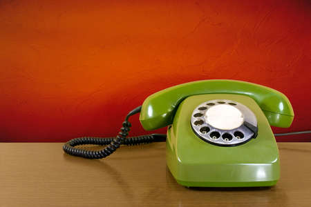 dialing: old green scratched phone against red wall background