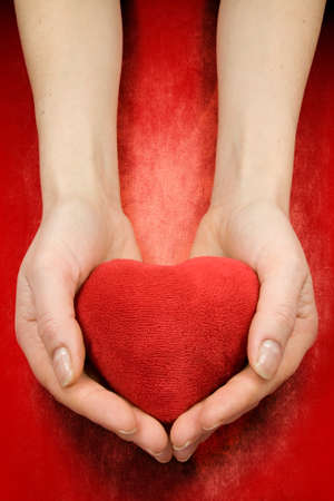 hands with heart on red grunge background Stock Photo - 8667699