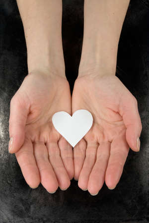 paper heart in a hands. Isolated on dark background photo