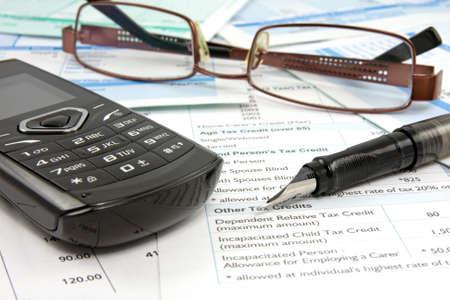 財源: ペン、携帯電話、メガネと財務報告 写真素材
