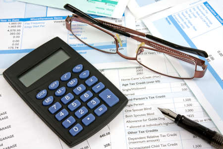 Business reports with calculator,eyeglasses and pen