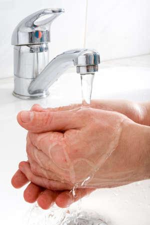 Human handen gewassen onder stroom van zuiver water