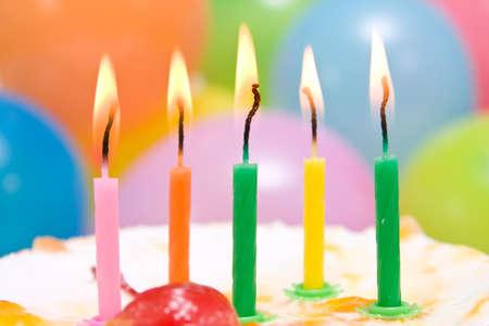 close-up van verjaardagstaart met kleurrijke kaarsen.
