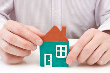 real estate concept. hands making  house from plasticine. Stock Photo - 9560825