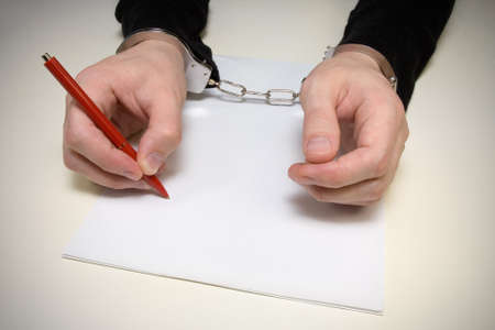 handcuffed  man  writing  a confession of the crime. photo