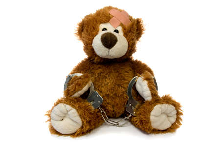 injured and handcuffed Teddy bear on white background. Stock Photo