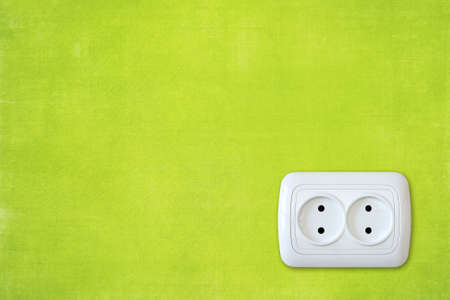 electric socket: bright green wall with white electric outlet.