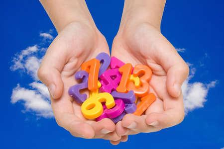 kind handen met kleurnummers op hemelachtergrond.