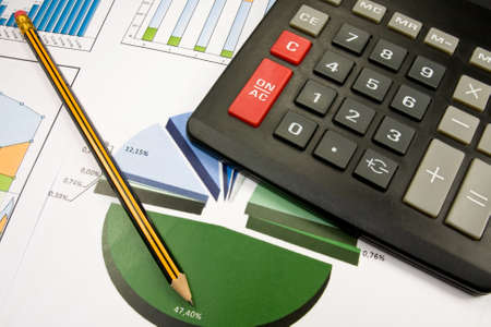 statements: Business concept. color charts ,pencil and  black calculator. Stock Photo