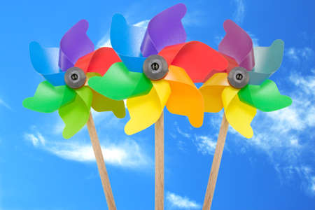 Three color pinwheel toys against blue sky. Stock Photo