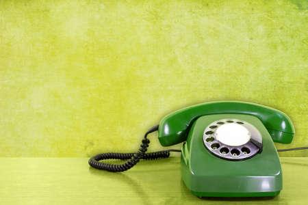 oude bekrast telefoon tegen groene muur achtergrond.
