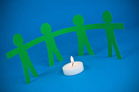 paper people holding hands and standing around burning candle photo