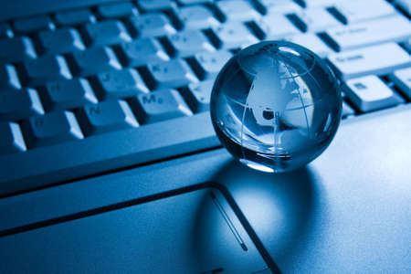 globalization concept. transparent globe on a laptop  keyboard  Stock Photo