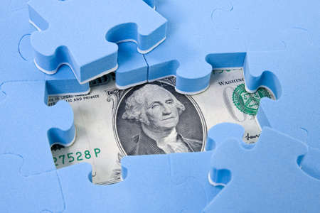 Hidden assets. Puzzle pieces on dollar background photo