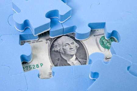 economie: Verborgen activa. Puzzelstukjes op dollar achtergrond