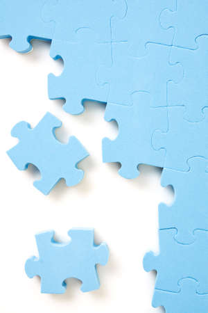 blue jigsaw puzzle pieces on white background photo