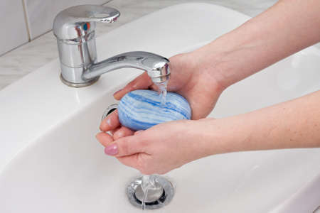 lavandose las manos: las manos del hombre que está lavando bajo el chorro de agua pura Foto de archivo