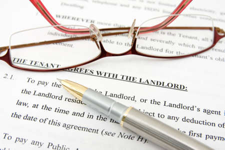 pen,glasses and tenant agreement with the landlord Stock Photo