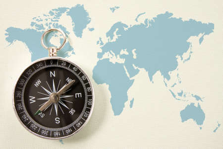 black compass on blue world map. concept for travel and tourism photo