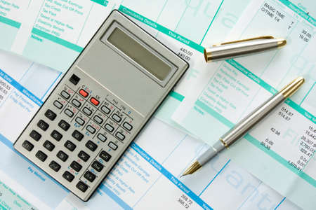 calculator,pen  and payroll summary details