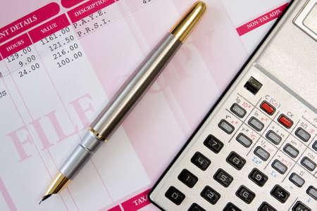 ink pen,calculator  and payroll summary details Standard-Bild