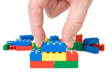 plastic bricks:  close-up of hand building a color plastic bricks Stock Photo