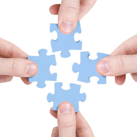 teamwork and partnership  concept. four hands connecting  puzzle photo