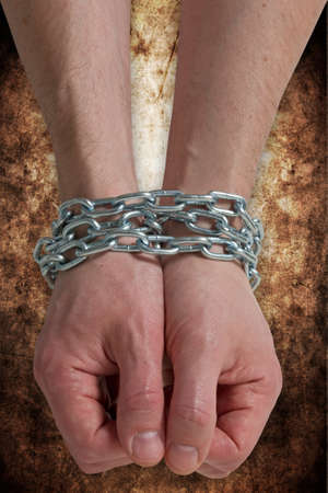 Hands chained together , isolated on a dirty background photo