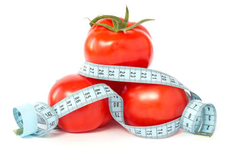 signify: tomatoes wrapped with measuring tape to signify weight loss Stock Photo