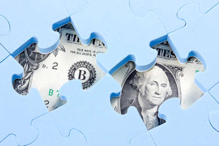 Hidden assets concept. Blue puzzle on one dollar bill  photo