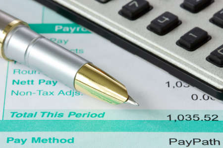 ink pen, calculator and payroll summary details