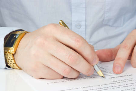 hand of businessman with pen, signing agreement photo