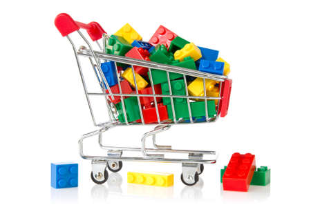 plastic bricks: color plastic bricks  in a shopping cart on white background