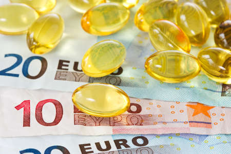 medical expenses: medical expenses concept. yellow pills and euro currency