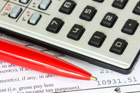 Calculator and red pen on the tax form Stock Photo - 17208293