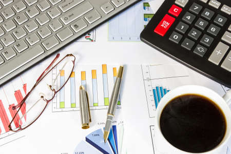 Desk of a businessman . Computer, business graphs, calculator, glasses,pen and coffee. Stock Photo - 17587140