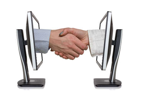 Two computer monitors and hands in handshaking, internet working concept, wireless communication, on-line business  Stock Photo