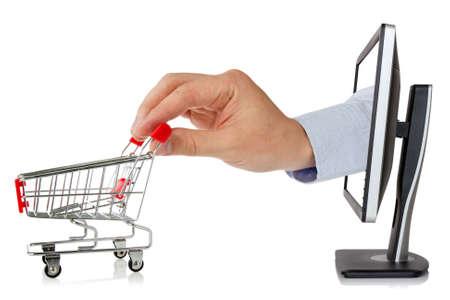 e-commerce concepto. mano se extiende de un monitor de ordenador con un carrito de la compra Foto de archivo