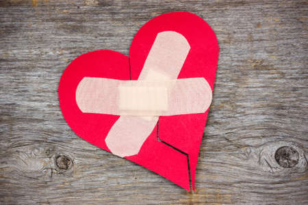 abandonment: Broken heart with plaster on the wooden background Stock Photo
