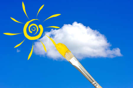 Paintbrush painting the yellow sun in a blue sky photo