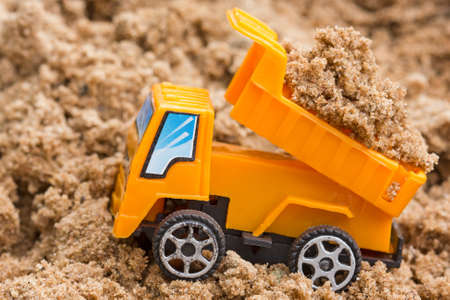 Dump truck unloads soil on the sand at a construction site  photo
