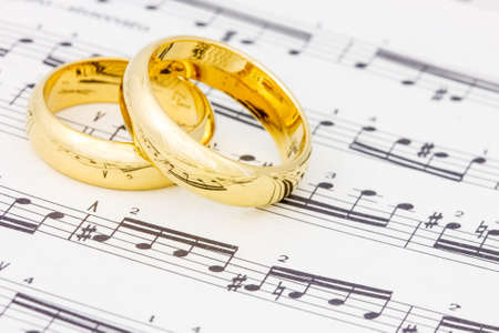 golden ring: Golden wedding rings on the old sheet music