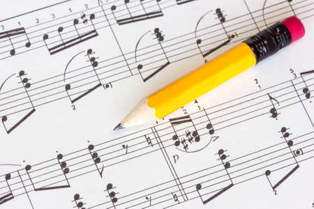 Sheet of musical notes with yellow pencil photo