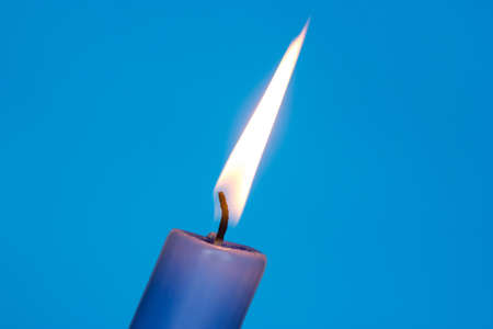 Flame of blue candle on the blue background photo