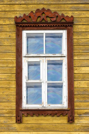 Window of old wooden yellow painted  house  photo