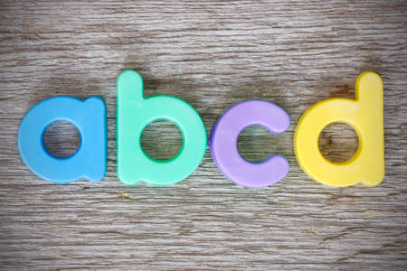 Letter magnets ABCD close up on wood background