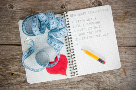 New years resolutions written on a notepad with a measure tape and heart Stock Photo