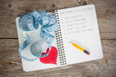 Nieuwe jaar resoluties geschreven op een notitieblok met een maatregel tape en het hart